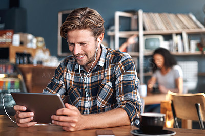 Buy stock photo Shot of a man wearing earphones while using a digital tablet in a cafe