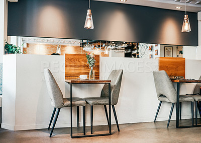 Buy stock photo Cropped shot of a coffee cup on a table and two chairs in an empty coffee shop during the day