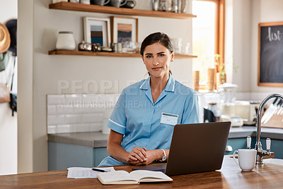 Buy stock photo Portrait of a young nurse working on a laptop in a nursing home