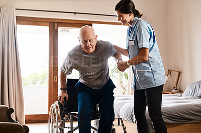 Buy stock photo Shot of a young nurse helping a senior man get up from a wheelchair in a retirement home