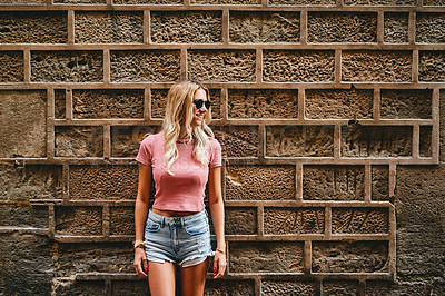 Buy stock photo Cropped shot of an attractive young woman standing alone against a brick wall during a vacation in Spain