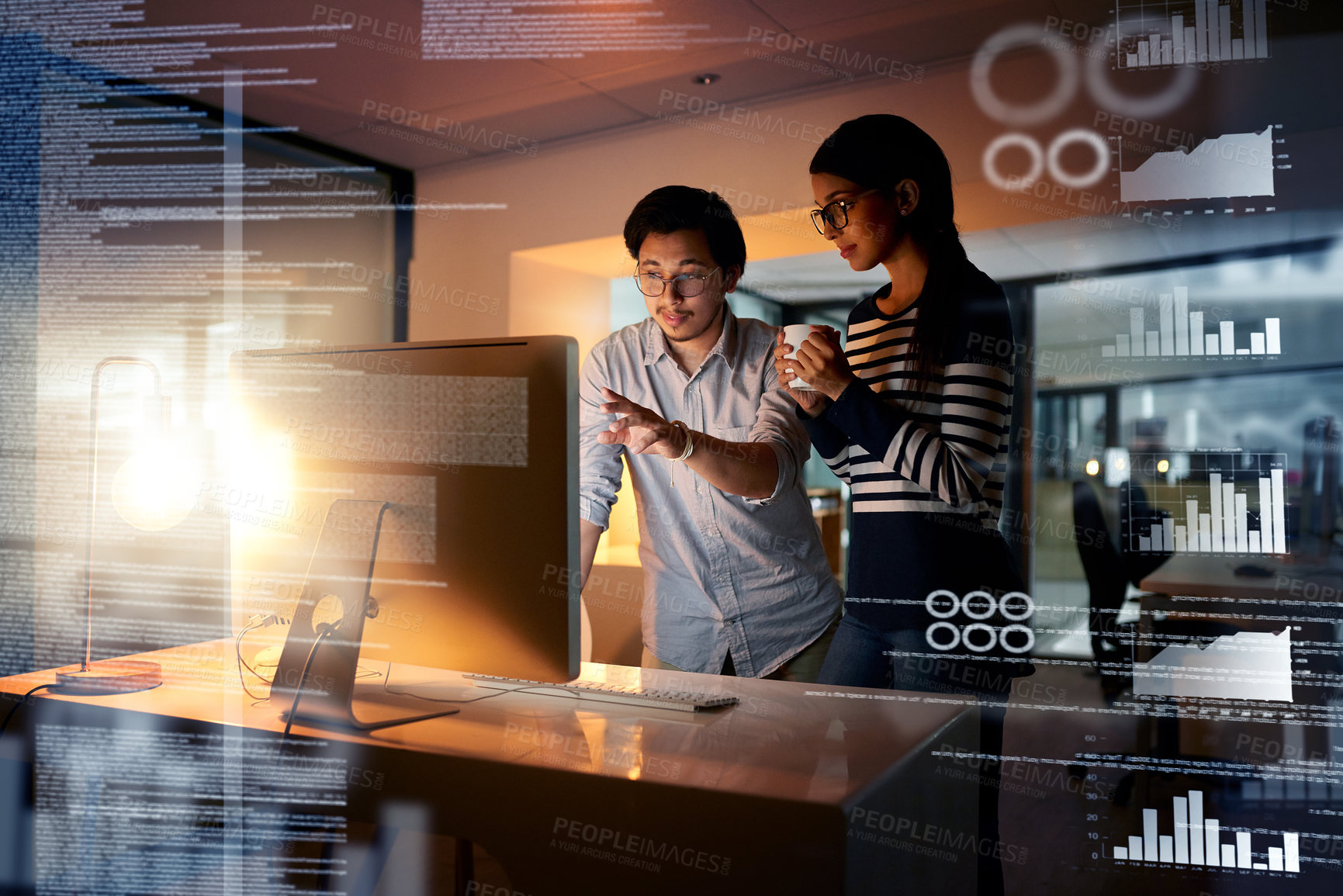 Buy stock photo Shot of colleagues connecting to a user interface while working in an office at night