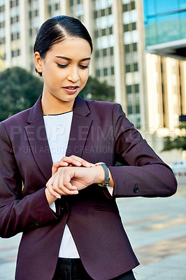 Buy stock photo Shot of an attractive young businesswoman checking the time on her wrist watch in the city