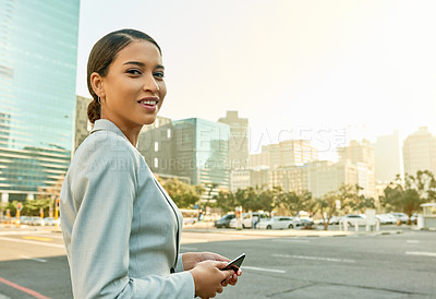 Buy stock photo Portrait of an attractive young businesswoman using a cellphone while standing in a parking lot in the city