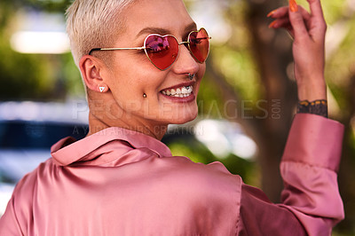 Buy stock photo Closeup portrait of an attractive and stylish young woman wearing sunglasses relaxing in a park outdoors