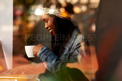 Buy stock photo Shot of an attractive young woman drinking coffee and using a laptop while relaxing inside a local cafe