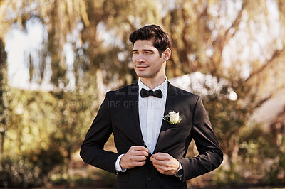 Buy stock photo Cropped shot of a handsome young bridegroom looking thoughtful while adjusting his suit on his wedding day