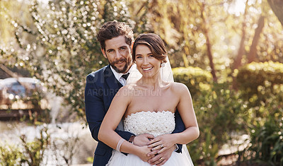 Buy stock photo Cropped portrait of an affectionate young bridegroom embracing his bride from behind while standing outdoors on their wedding day