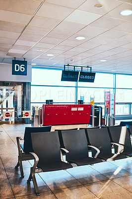 Buy stock photo Cropped shot of an empty waiting area and a red ticket counter in an international airport during the day