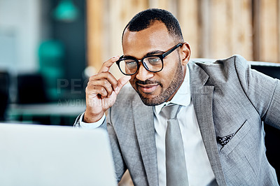 Buy stock photo Cropped shot of a handsome young businessman sitting alone in his office and smirking while using his laptop