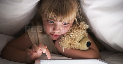 Buy stock photo Shot of a young girl using a digital tablet while lying in bed at night