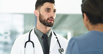 Buy stock photo Cropped shot of a handsome young male doctor consulting a female patient while standing in a hospital