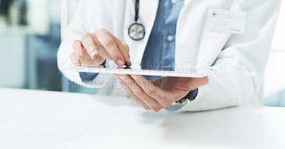 Buy stock photo Cropped shot of an unrecognizable male doctor using a digital tablet while sitting in his office