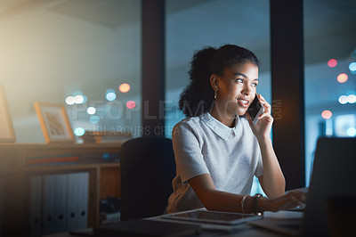 Buy stock photo Shot of a businesswoman talking on her cellphone while working late at the office