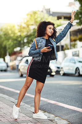 Buy stock photo Full length shot of an attractive young woman using her cellphone while hailing down a taxi in the city