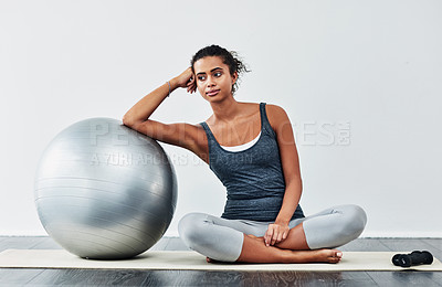 Buy stock photo Shot of a sporty young woman leaning against a exercise ball