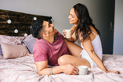 Buy stock photo Shot of a happy young couple having coffee together in the bedroom at home