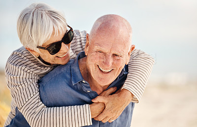 Buy stock photo Shot of a senior couple enjoying a piggyback ride at the beach