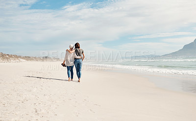 Buy stock photo Rearview shot of a young woman going for a walk along the beach with her elderly mother