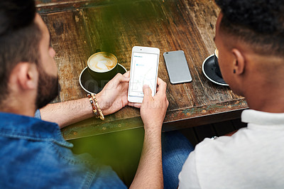 Buy stock photo Shot of two young men chatting and using their smartphones in a cafe