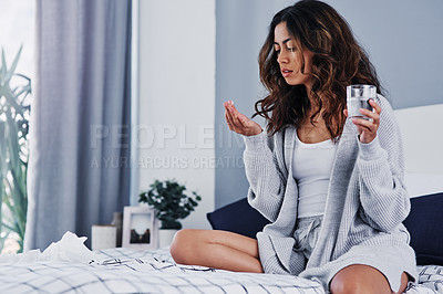 Buy stock photo Cropped shot of an attractive young woman sitting on her bed at home and taking painkillers with water