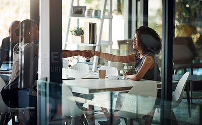 Buy stock photo Shot of two attractive young businesswomen shaking hands during a boardroom meeting at work