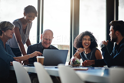 Buy stock photo Shot of a group of businesspeople using a laptop during their boardroom meeting at work