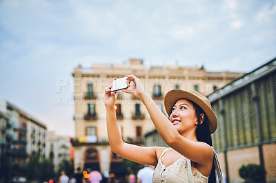 Buy stock photo Cropped shot of an attractive young woman standing in the city and taking a photograph with her cellphone