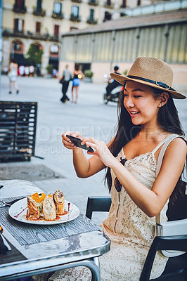 Buy stock photo Cropped shot of an attractive young woman sitting alone and taking a picture of her meal at a cafe