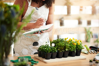 Buy stock photo Cropped shot of an unrecognizable young female botanist making notes while working in her florist