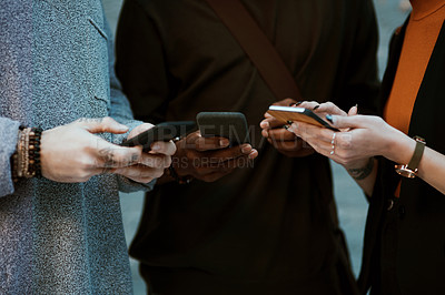 Buy stock photo Cropped shot of a group of unrecognizable creative businesspeople using their cellphones outside in the city