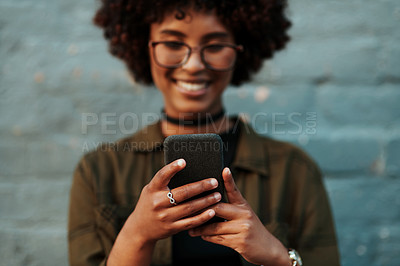 Buy stock photo Shot of an attractive young creative businesswoman using a cellphone outside in the city