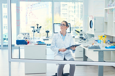 Buy stock photo Cropped shot of a focused young female scientist reading from her notebook while looking at calculations on a glass wall inside of a laboratory