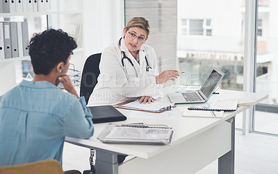 Buy stock photo Cropped shot of an attractive young female doctor using a laptop while having a discussion with a female patient in her office