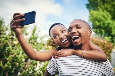 Buy stock photo Cropped shot of a happy young couple taking a selfie outside