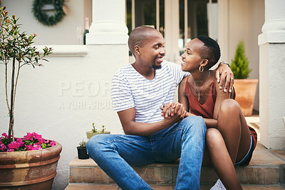 Buy stock photo Shot of an affectionate couple sitting on their front door steps