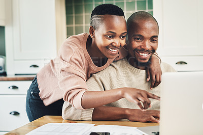 Buy stock photo Shot of a happy young couple using a laptop while relaxing together at home