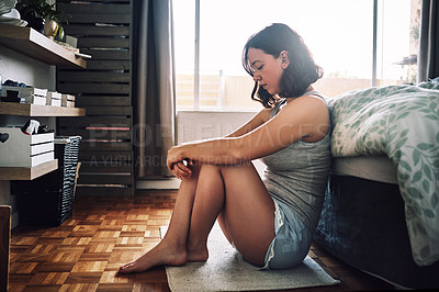 Buy stock photo Full length shot of an attractive young woman looking depressed while sitting on the floor in her bedroom at home