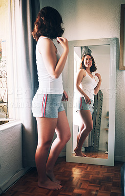 Buy stock photo Full length shot of an attractive young woman admiring herself while standing in front of the mirror in her bedroom at home