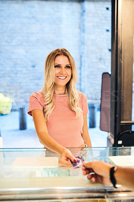 Buy stock photo Shot of a young woman paying at the checkout of an ice cream parlour with a credit card