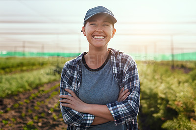Buy stock photo Cropped portrait of an attractive young female farmer standing with her arms crossed while working on the farm