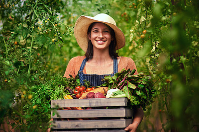 Buy stock photo Portrait of an attractive young female farmer carrying a crate of freshly picked vegetables at her farm