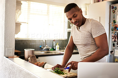 Buy stock photo Cropped shot of a handsome young man using a laptop while chopping vegetables in his kitchen at home