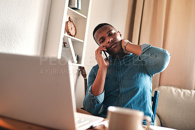 Buy stock photo Cropped shot of a handsome young businessman sitting and using his cellphone at home while suffering from neck ache