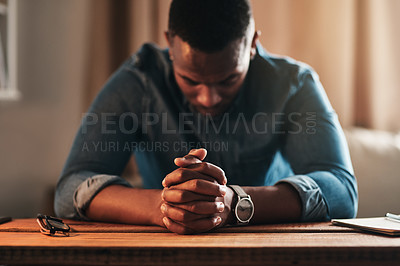 Buy stock photo Cropped shot of a handsome young businessman sitting with his hands together in his home office and praying