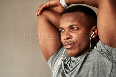 Buy stock photo Cropped shot of a sporty young man stretching at home