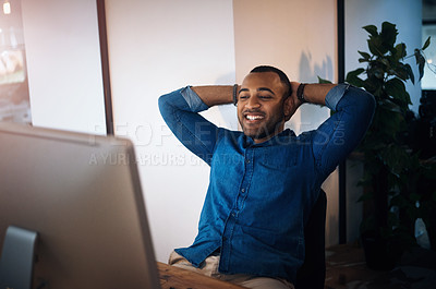 Buy stock photo Shot of a young businessman taking a break at his desk while working in an office at night
