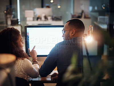 Buy stock photo Rearview shot of two businesspeople working together on a computer in an office at night