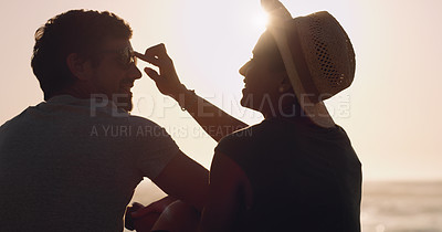 Buy stock photo Cropped shot of an affectionate young woman adjusting her boyfriend's sunglasses while sitting at the beach at sunset