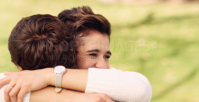 Buy stock photo Cropped shot of an affectionate young woman hugging her boyfriend while standing in a park during the day